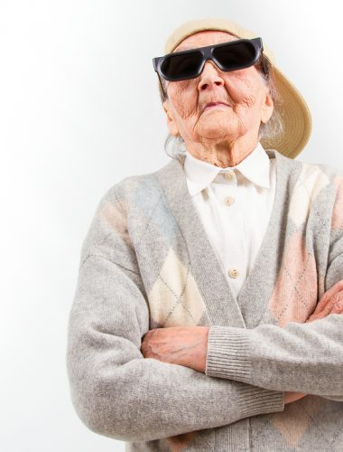 Funny grandma's studio portrait wearing eyeglasses and baseball cap who stands for her right isolated on white